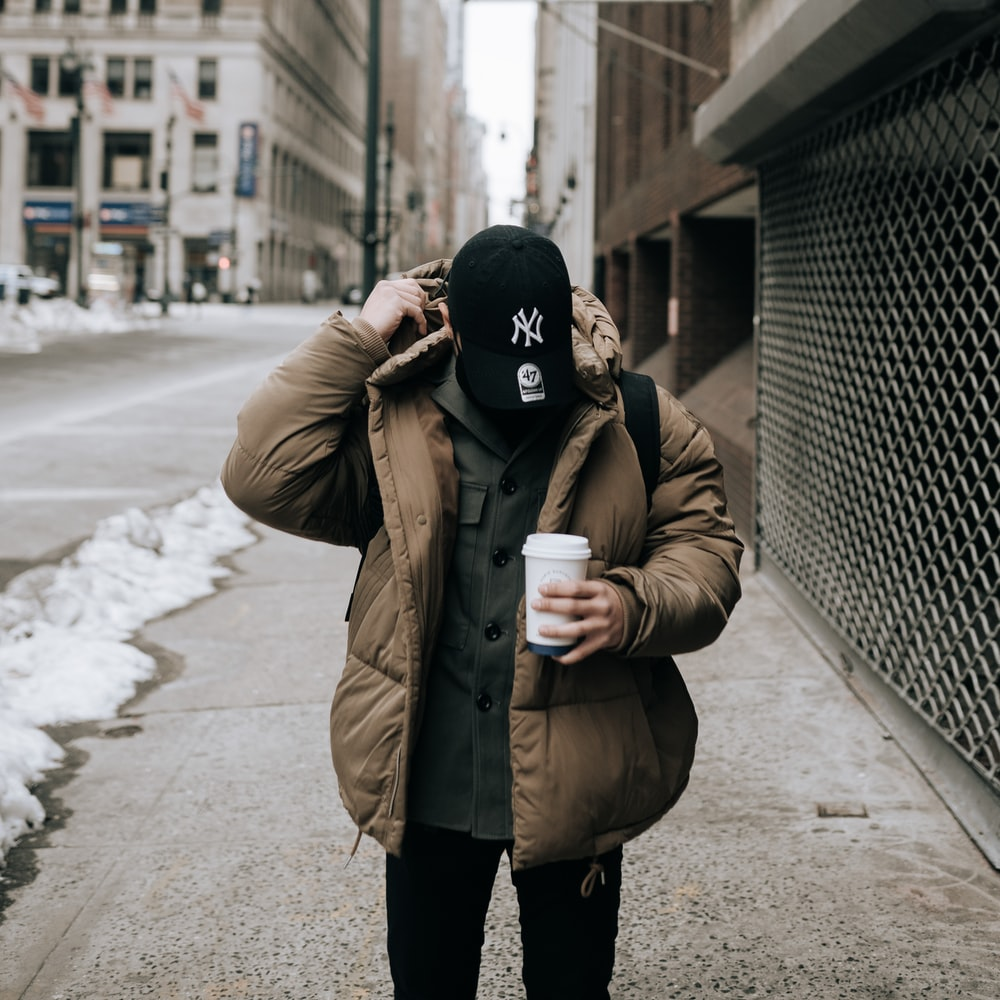 woman in brown coat and black knit cap standing on sidewalk during daytime