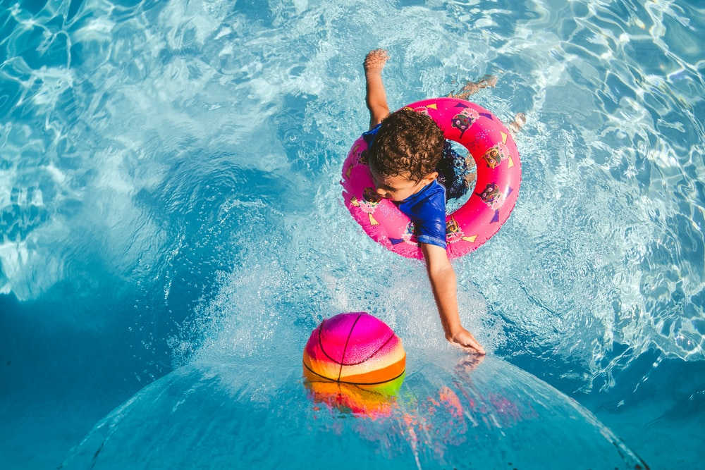 girl in blue tank top and blue shorts holding pink inflatable ring on water