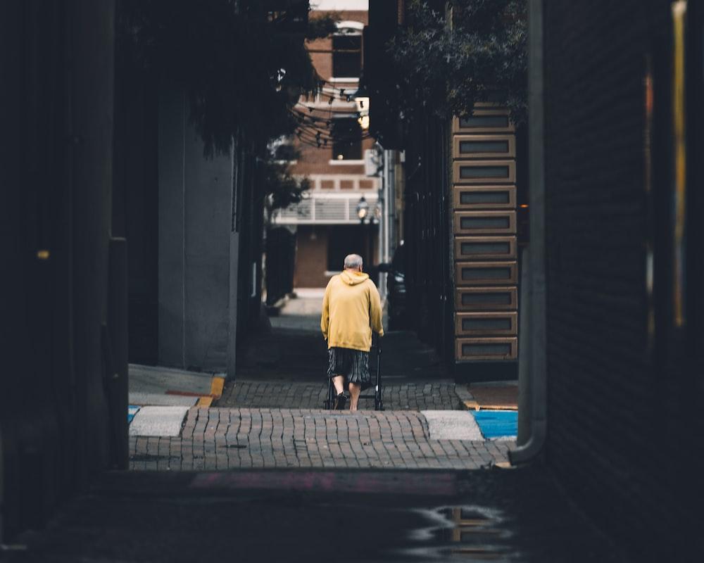 man in white dress shirt and black pants walking on sidewalk during night time