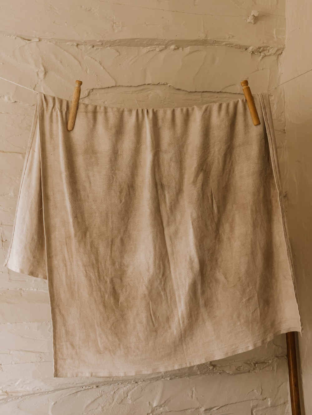 white bath towel on brown wooden clothes hanger