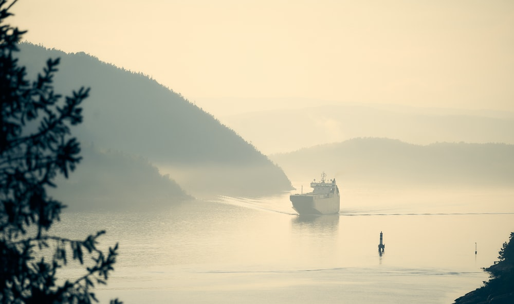 white boat on body of water during foggy weather