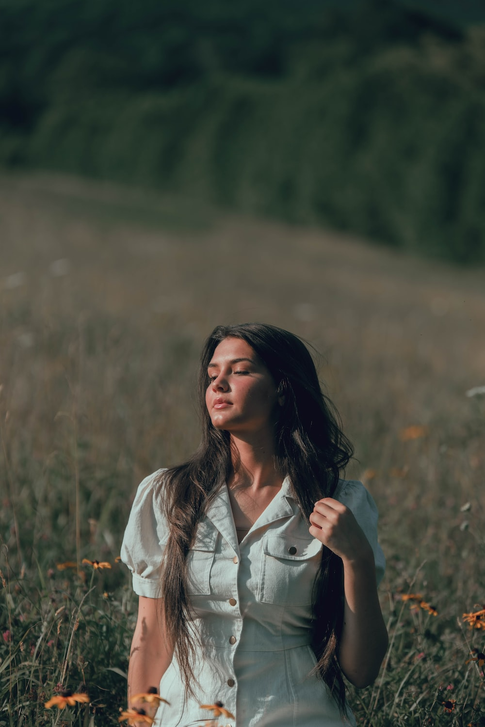 woman in white button up shirt standing on brown grass field during daytime