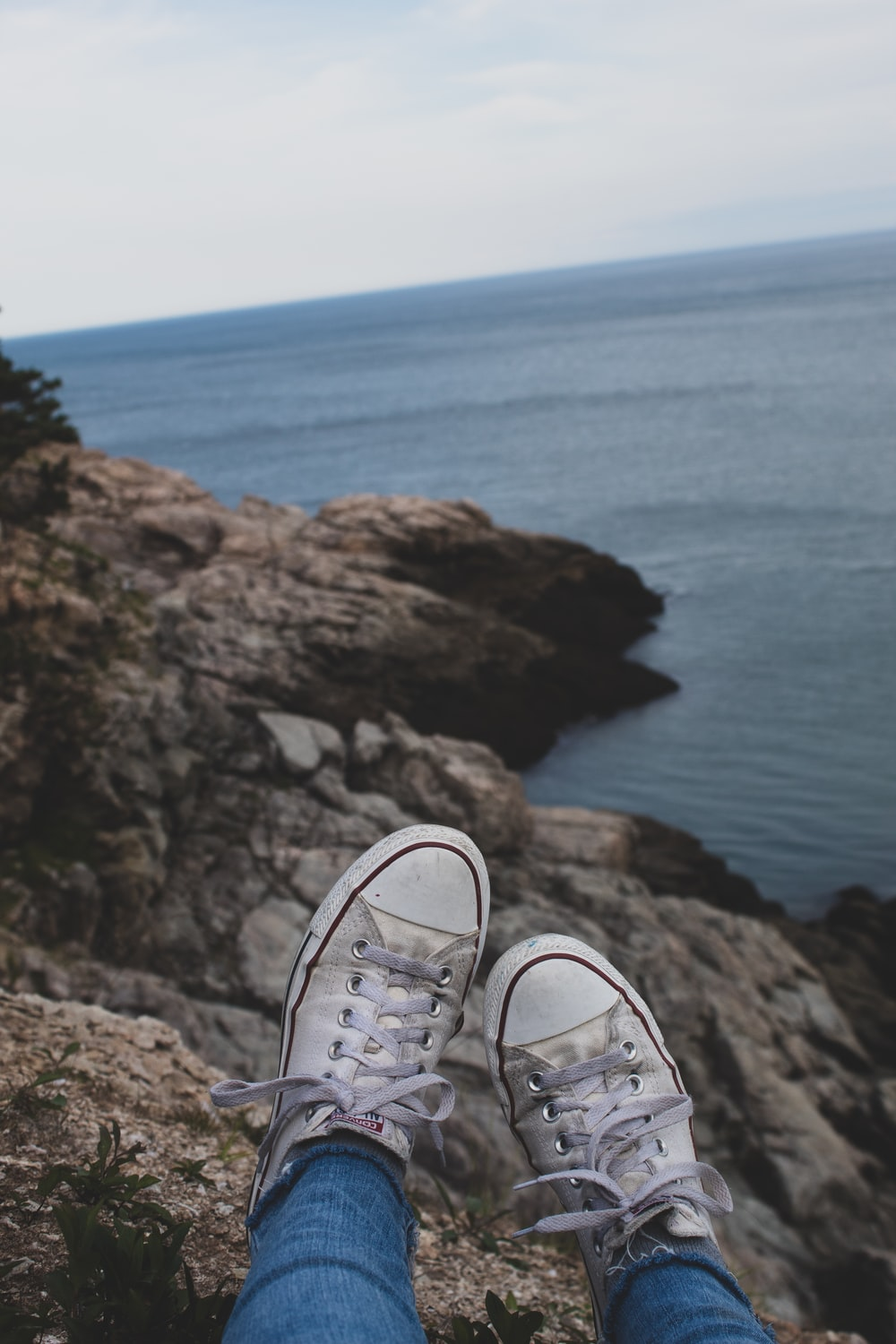 person wearing gray and white sneakers standing on brown rock formation near body of water during