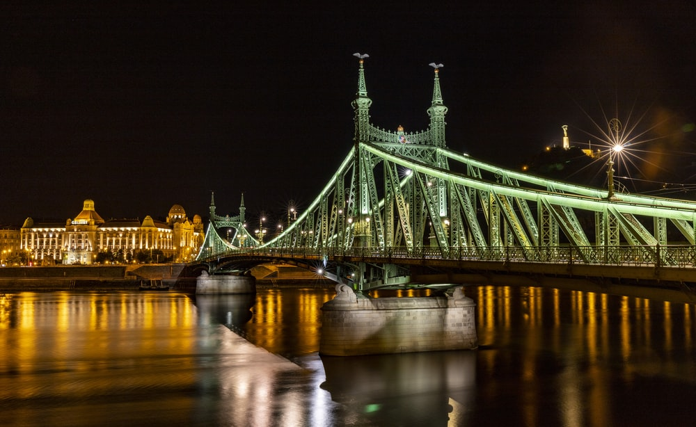green bridge over river during night time