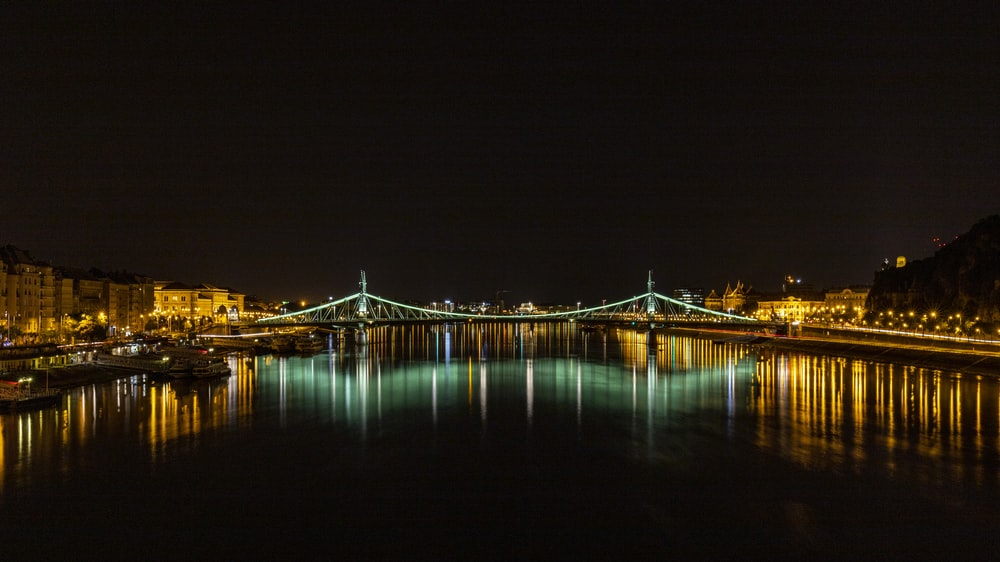 blue bridge over water during night time