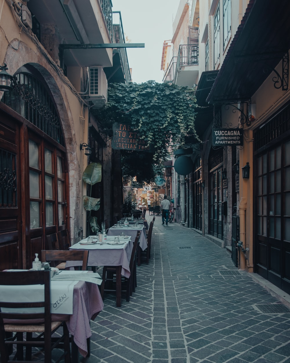 brown wooden table and chairs set on street during daytime