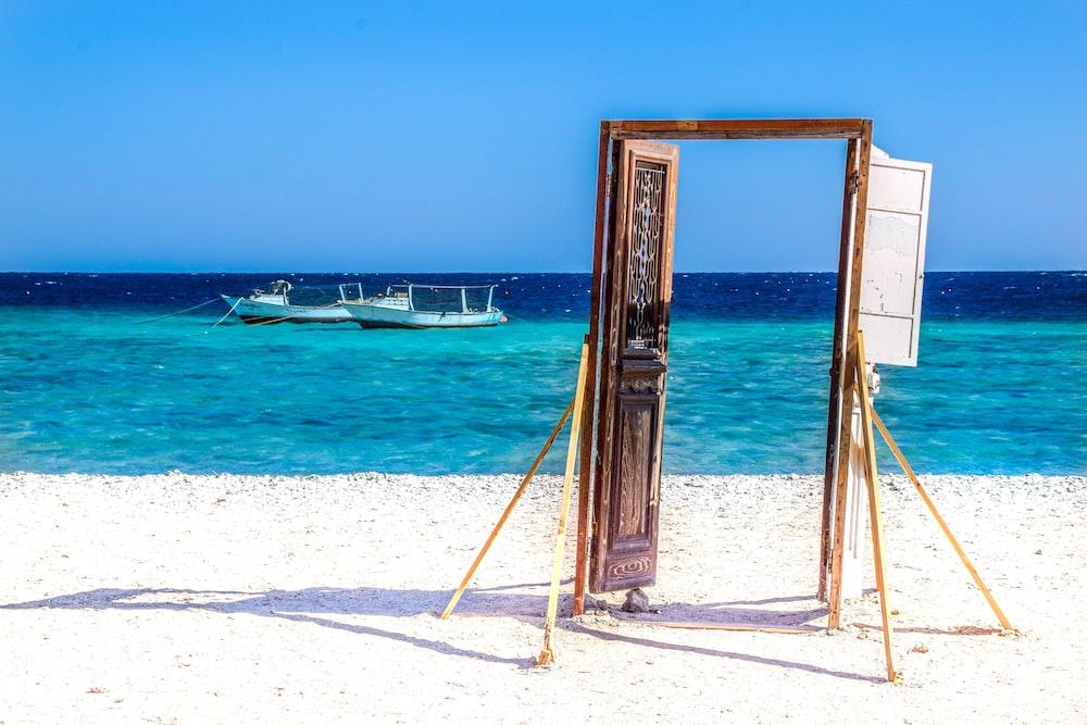 brown wooden frame on white sand beach during daytime