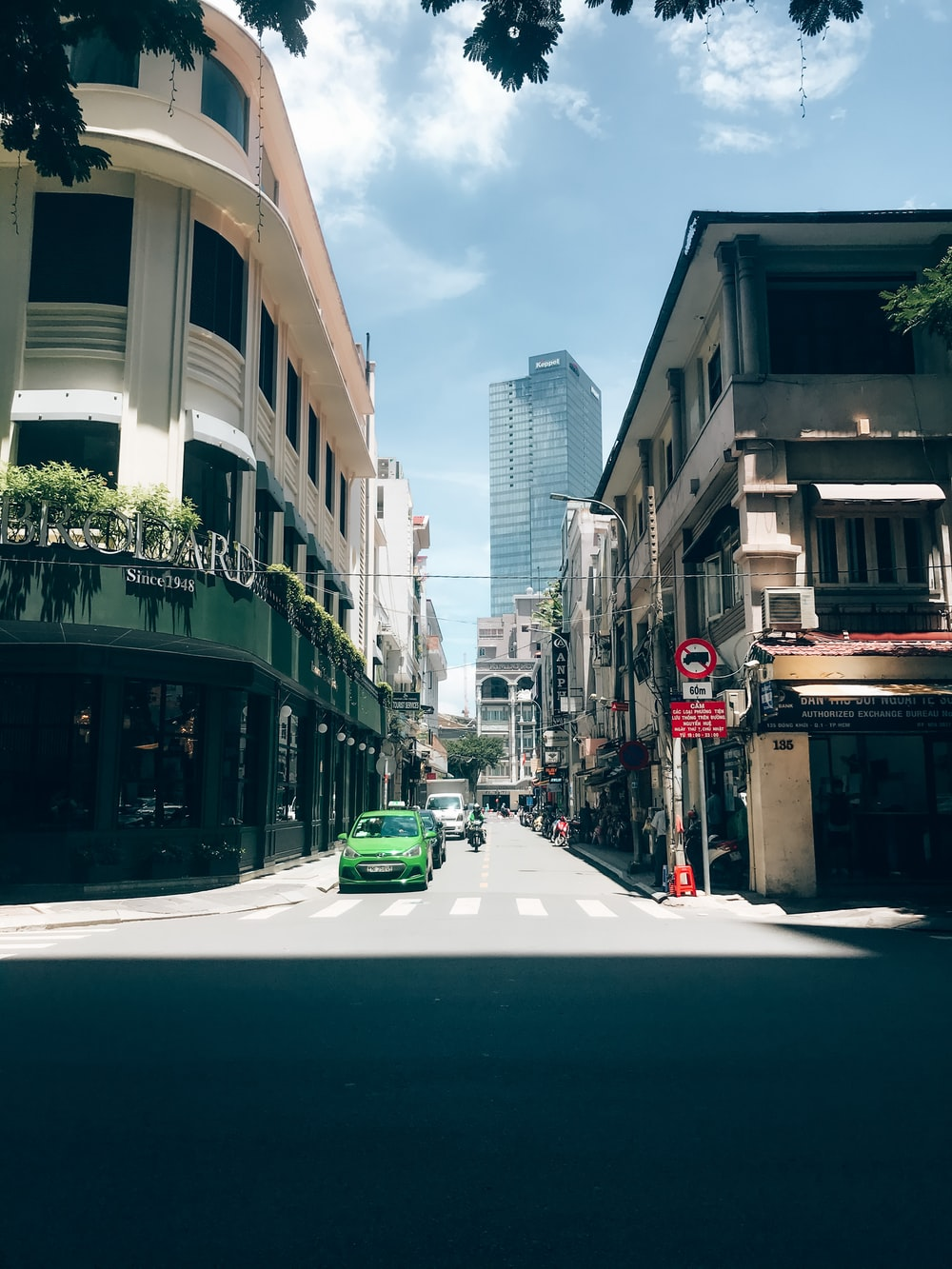 cars parked on side of the road in between buildings during daytime