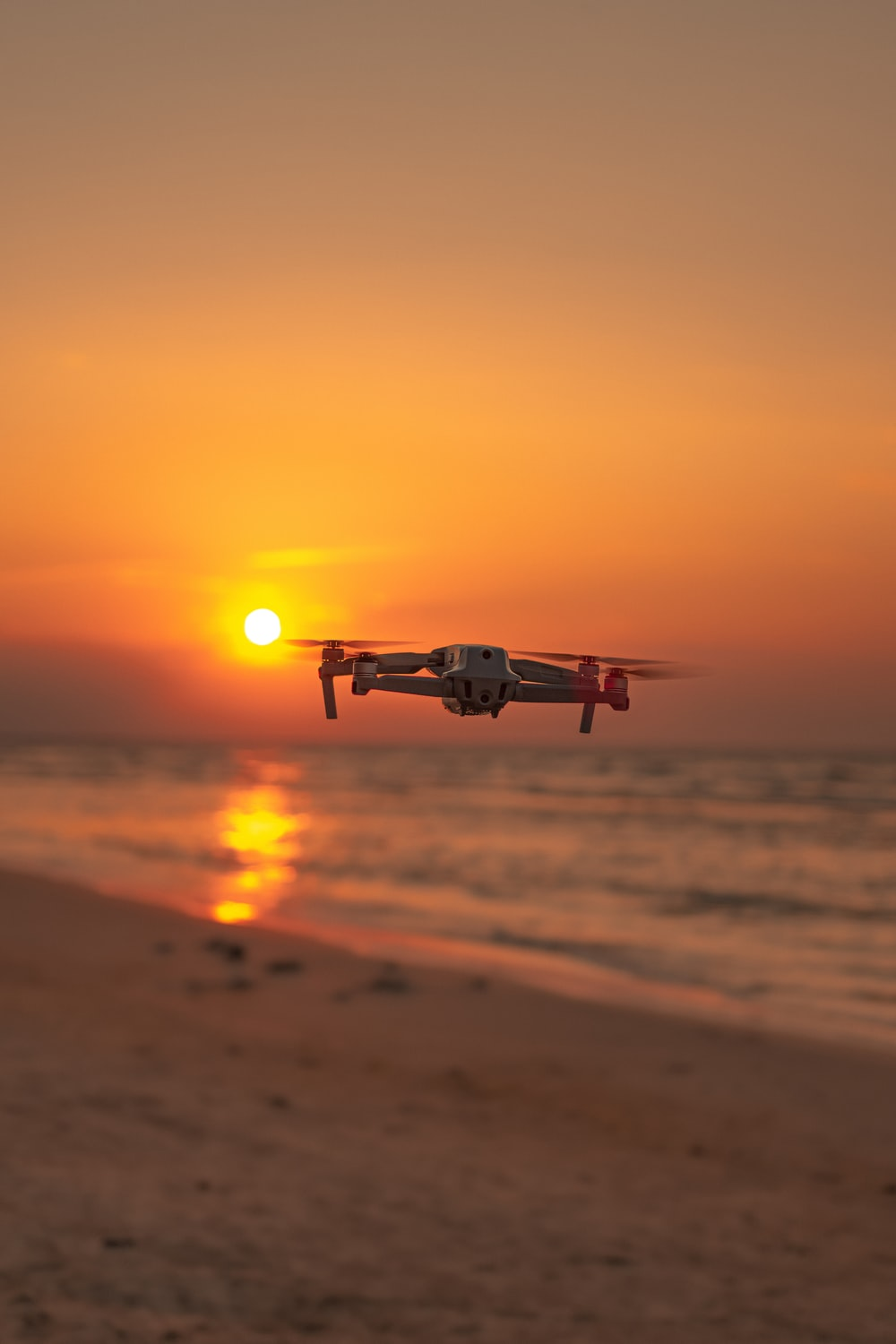 white drone flying over the beach during sunset