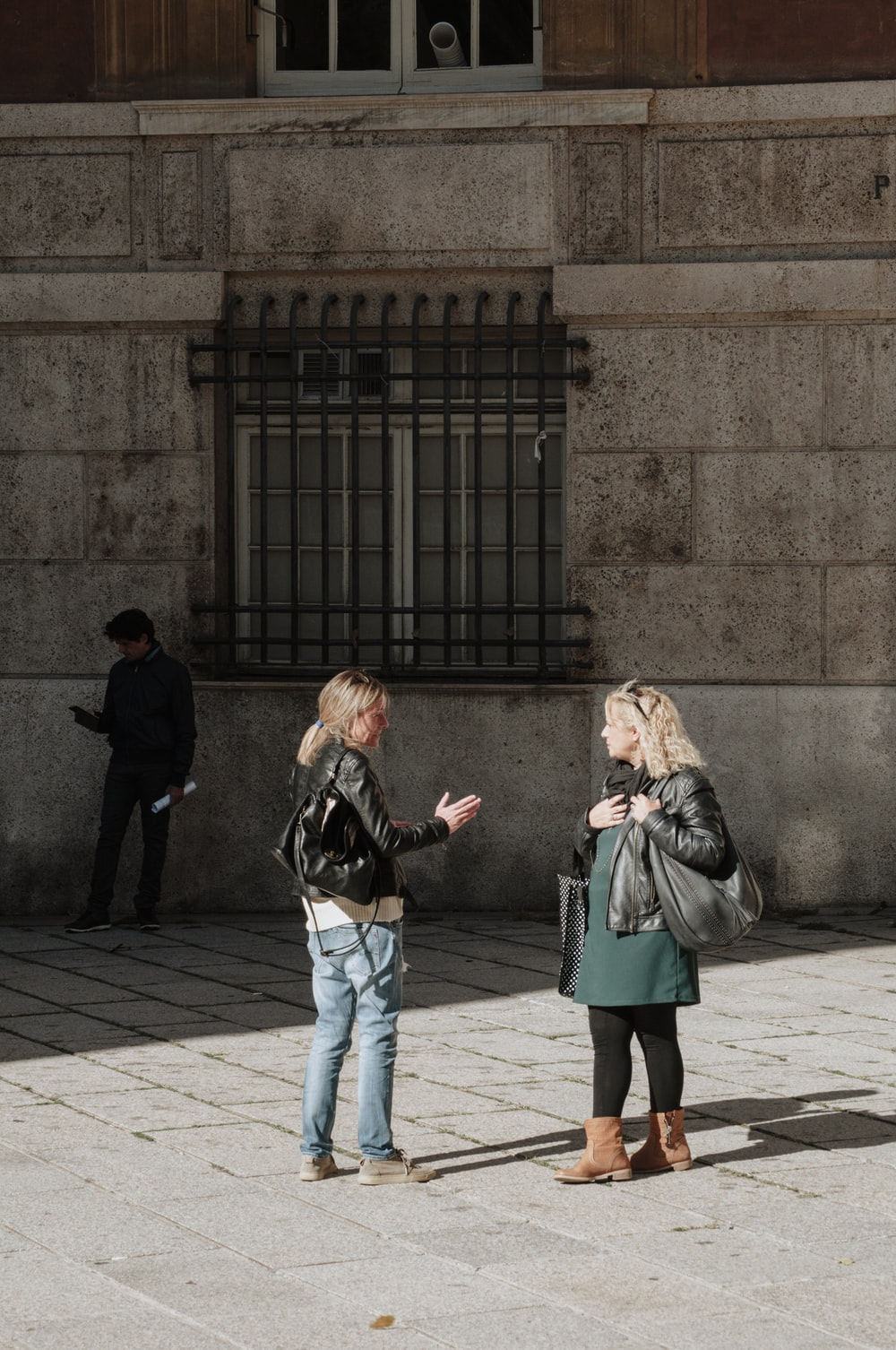 woman in black jacket and blue denim jeans standing beside woman in gray coat