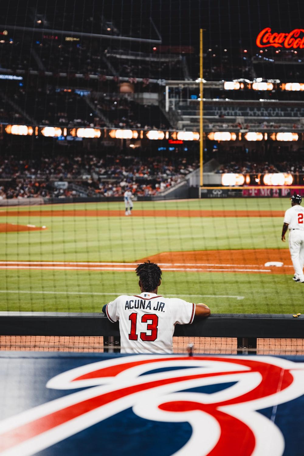 man in white jersey shirt playing baseball