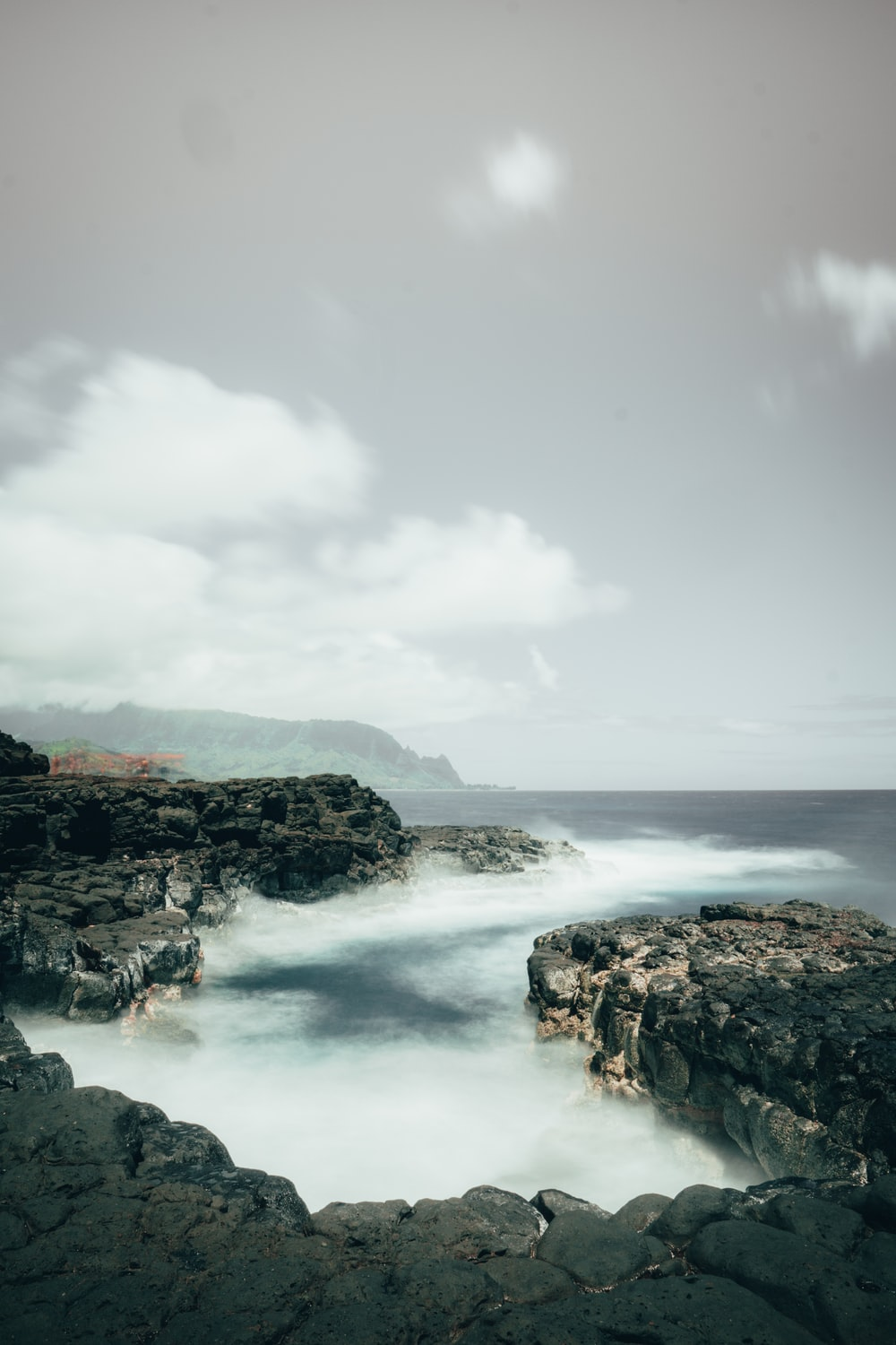 ocean waves crashing on rocky shore under white cloudy sky during daytime