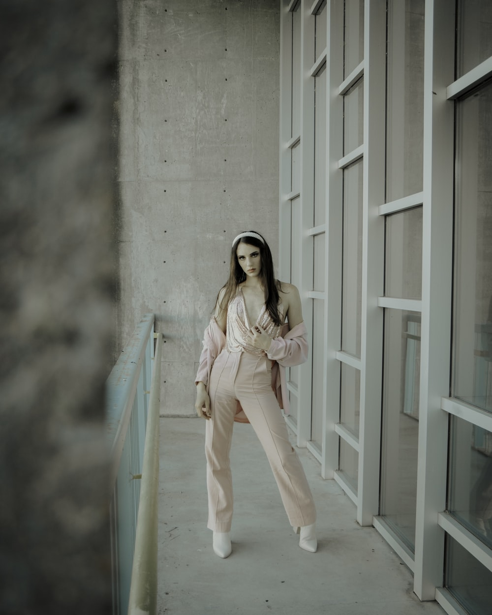 woman in pink long sleeve shirt and white pants standing on white wooden floor