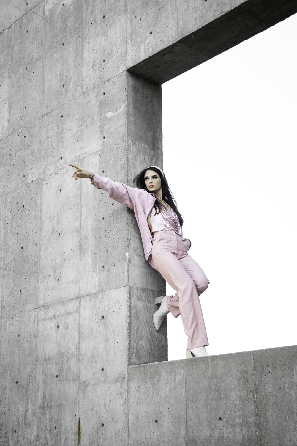 woman in pink coat standing on gray concrete wall