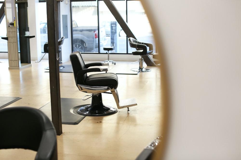 black leather barber chair near glass window