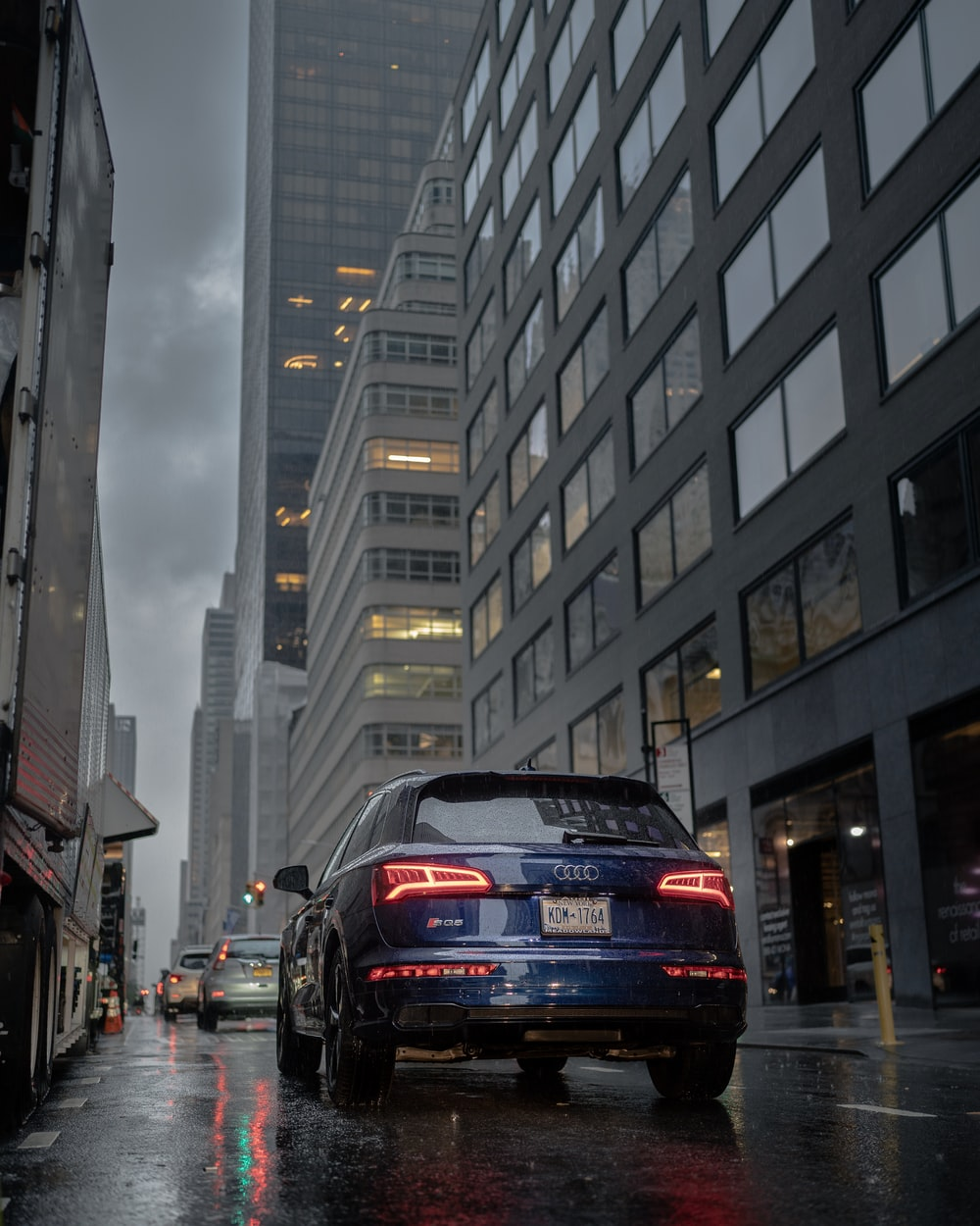 black audi a 4 on road in between high rise buildings during daytime