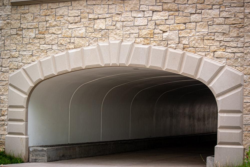 white concrete stairs near brown brick wall
