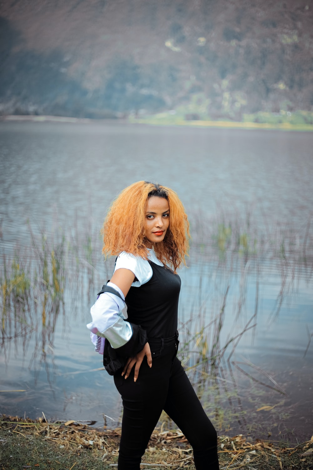 woman in black blazer holding white cup standing near body of water during daytime