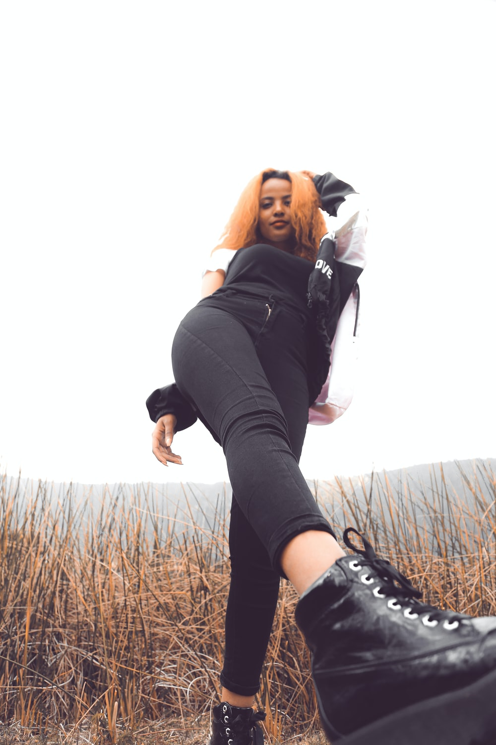 woman in black jacket and black leggings standing on brown grass field during daytime