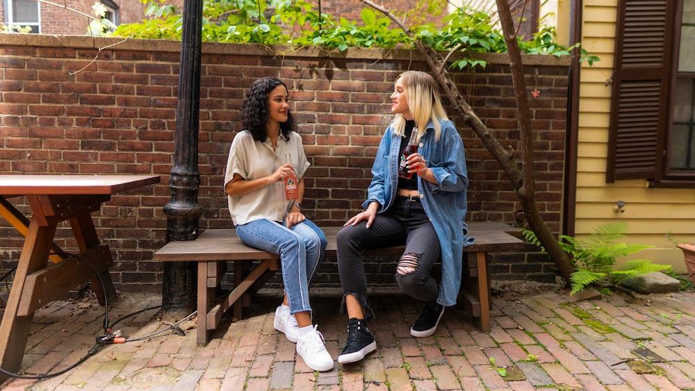 2 women sitting on brown wooden bench