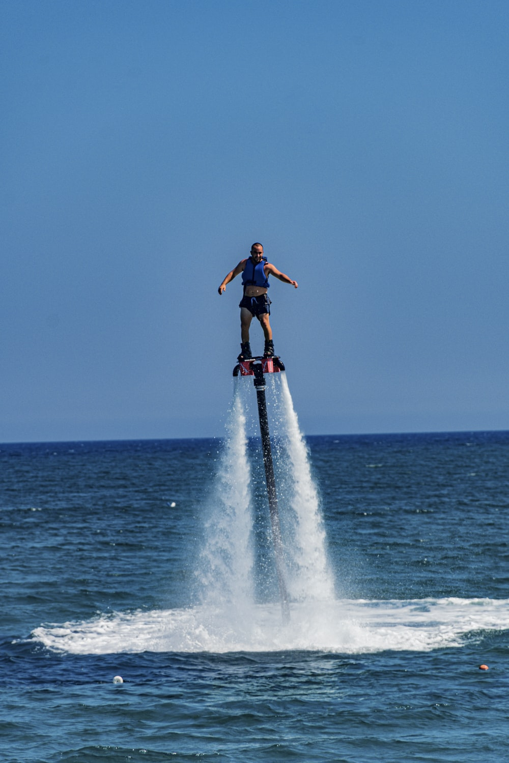 woman in black tank top and blue denim jeans standing on white surfboard on sea waves