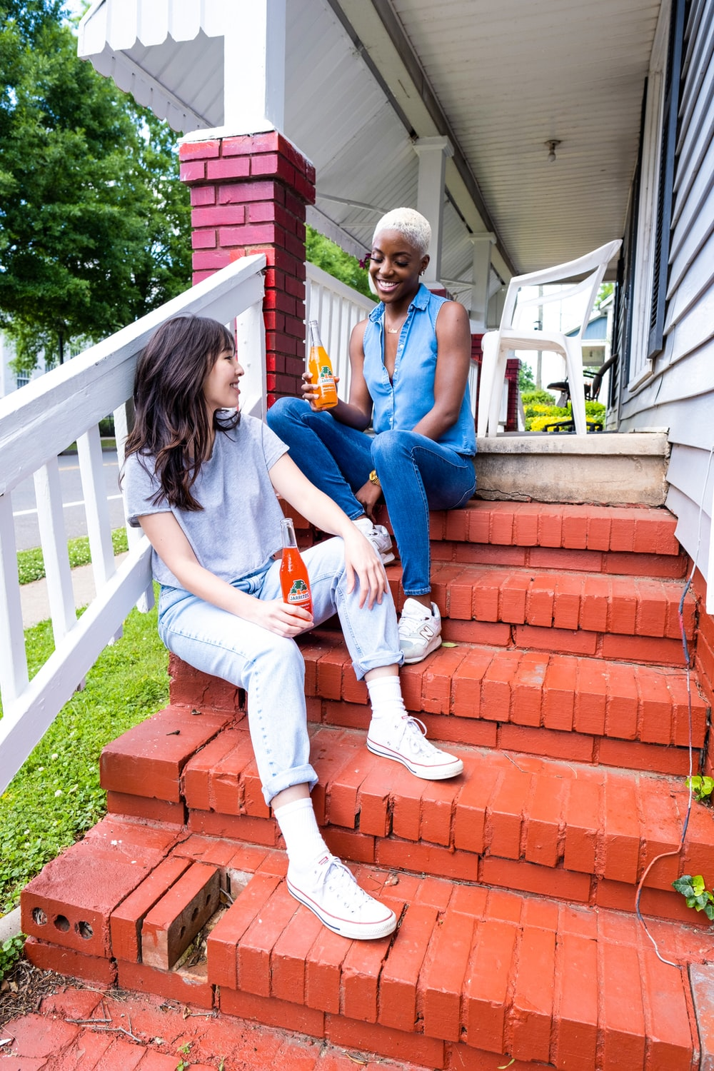 man and woman sitting on red concrete stairs