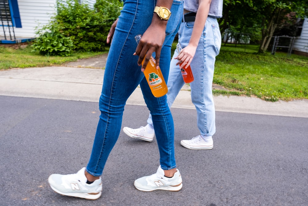 2 person holding orange and blue plastic bottle