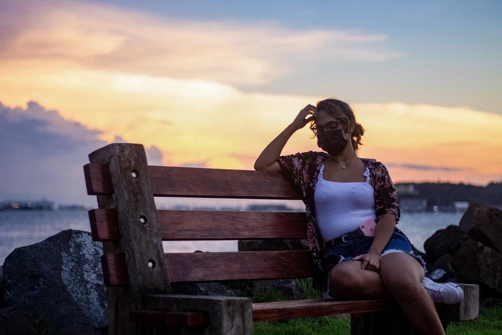 woman in white tank top sitting on brown wooden bench during daytime