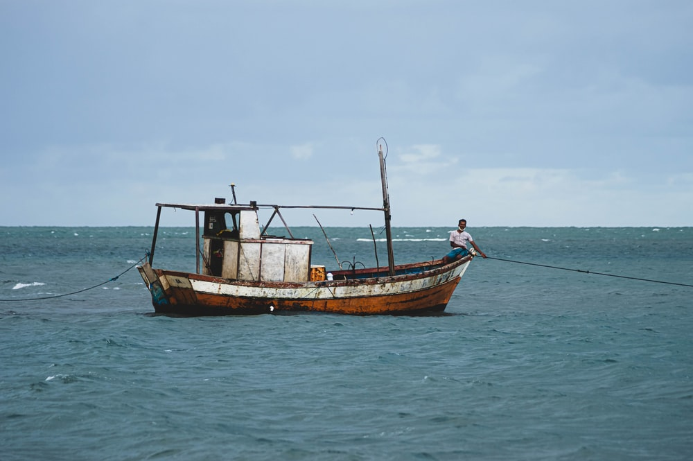 brown and black boat on sea during daytime