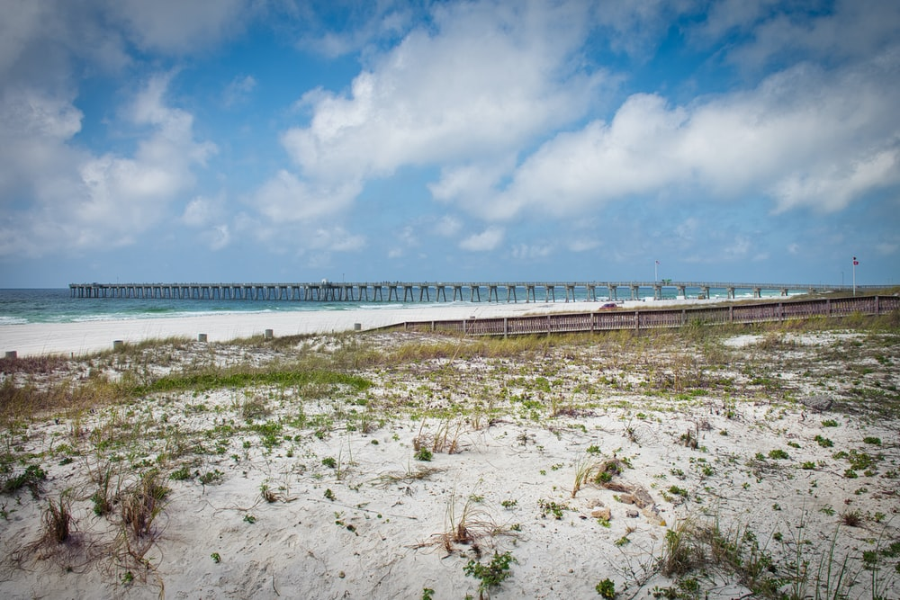 white sand beach with bridge under blue sky and white clouds during daytime