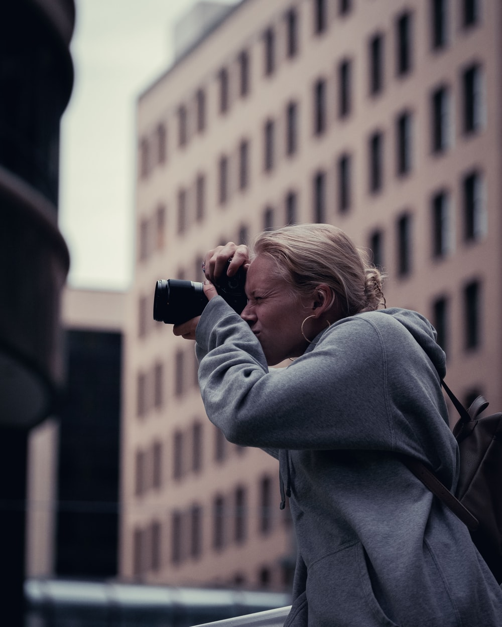 woman in gray hoodie holding black dslr camera