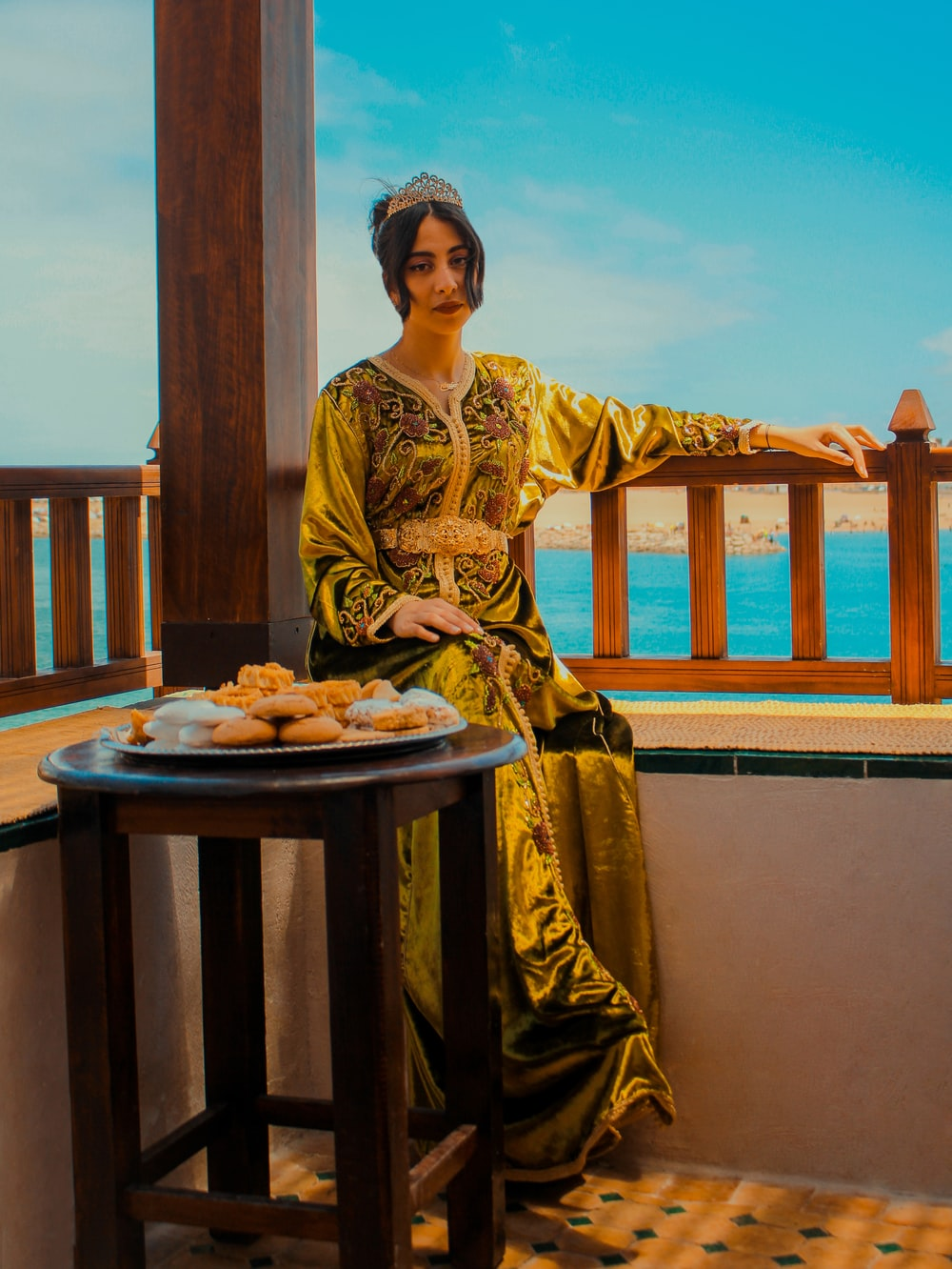 woman in yellow and brown long sleeve dress sitting on brown wooden chair