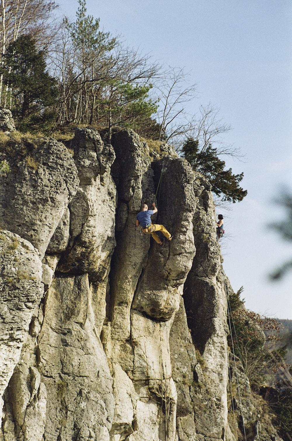man in yellow jacket climbing on rocky mountain during daytime