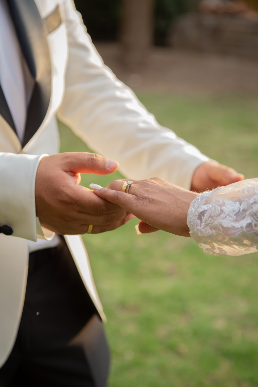 man in black suit jacket holding womans hand