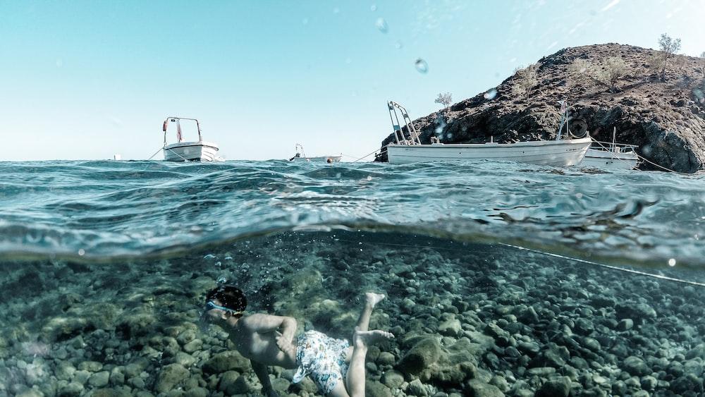 woman in white bikini swimming on sea during daytime