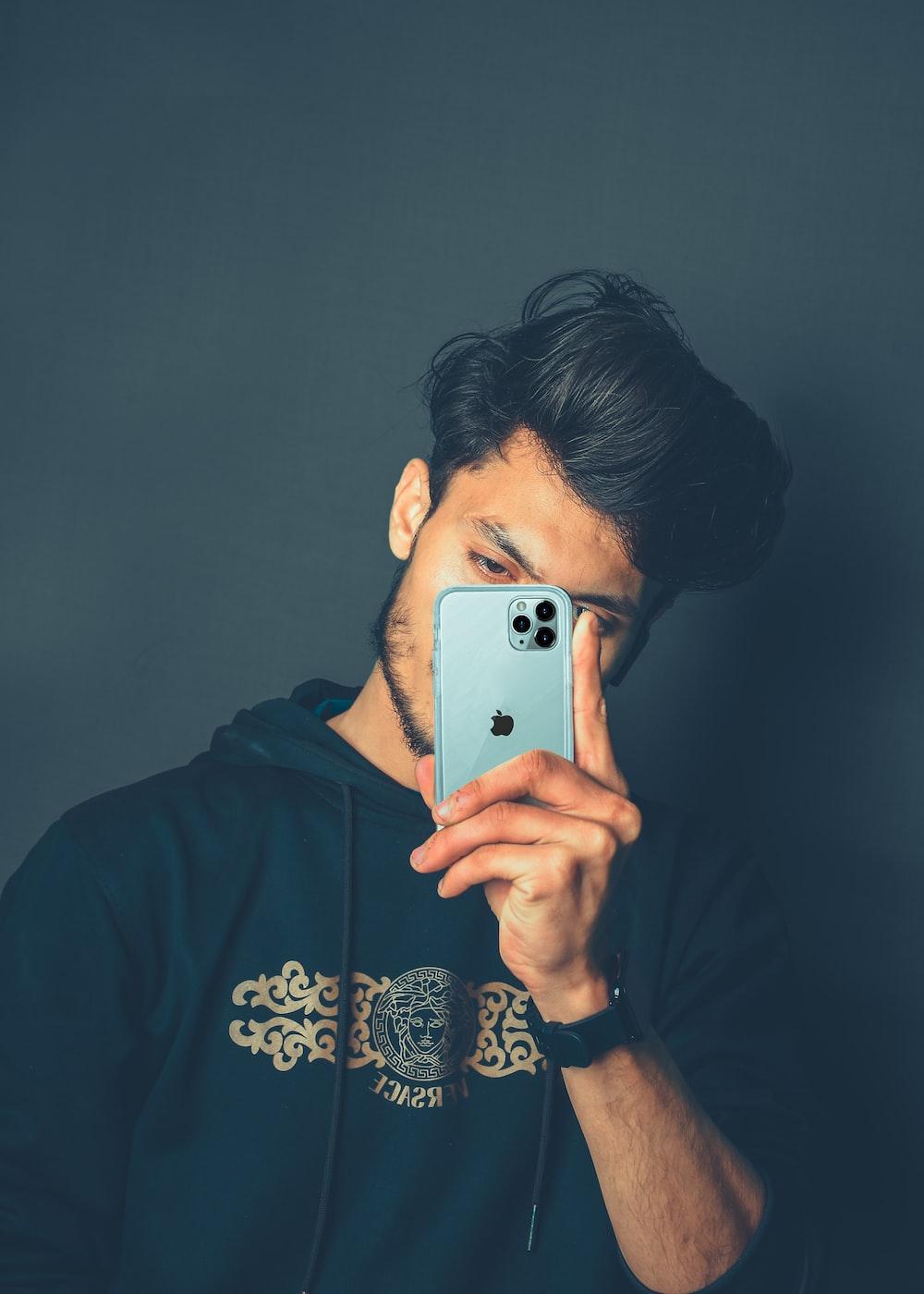 man in black hoodie holding silver iphone 6