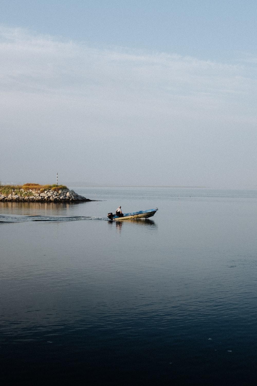 man in blue kayak on sea during daytime