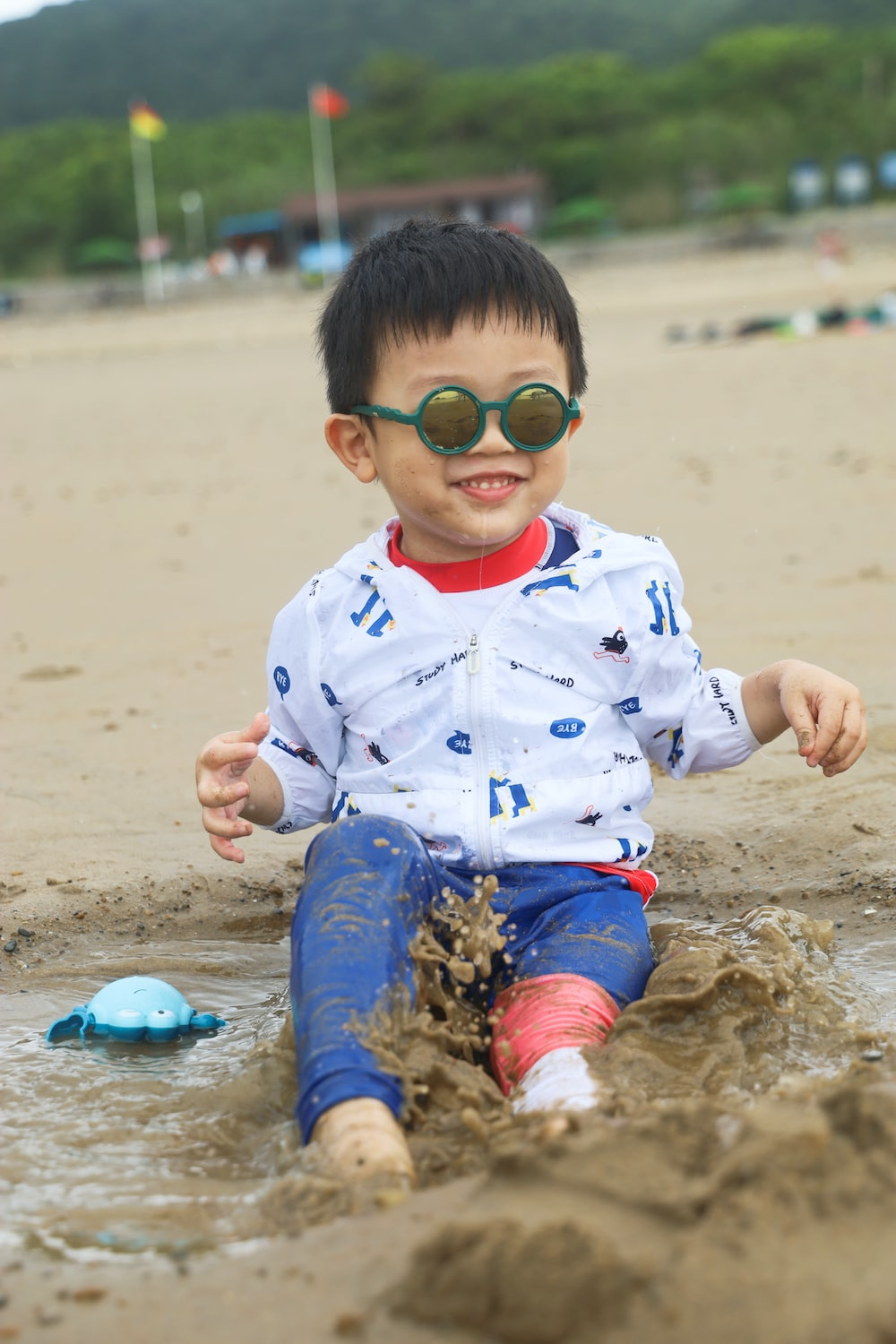 boy in white and blue star print polo shirt and brown pants sitting on brown sand