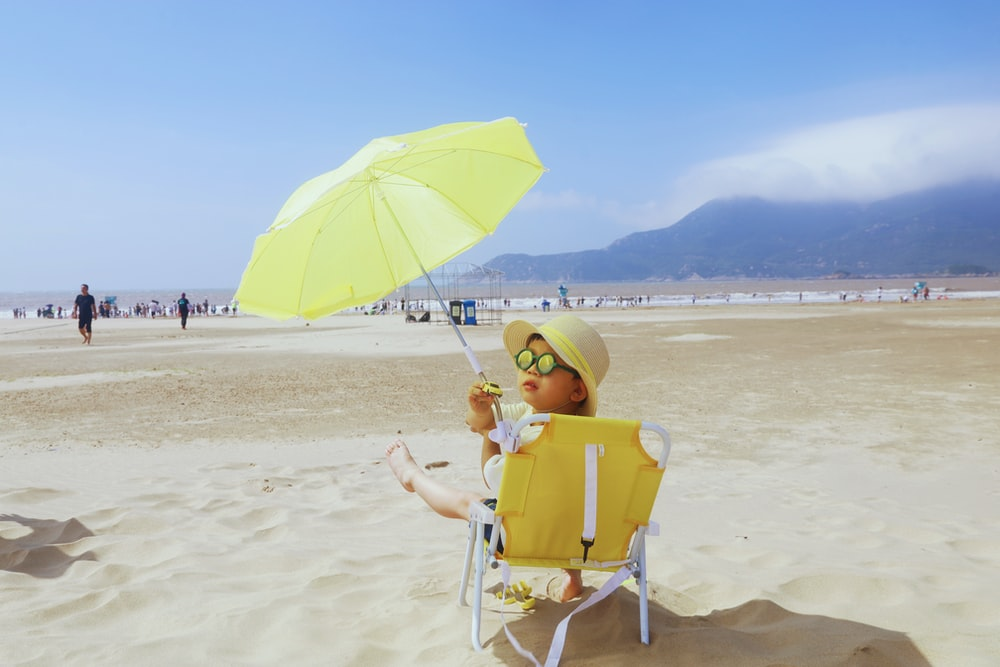woman in yellow sun hat sitting on green chair on beach during daytime