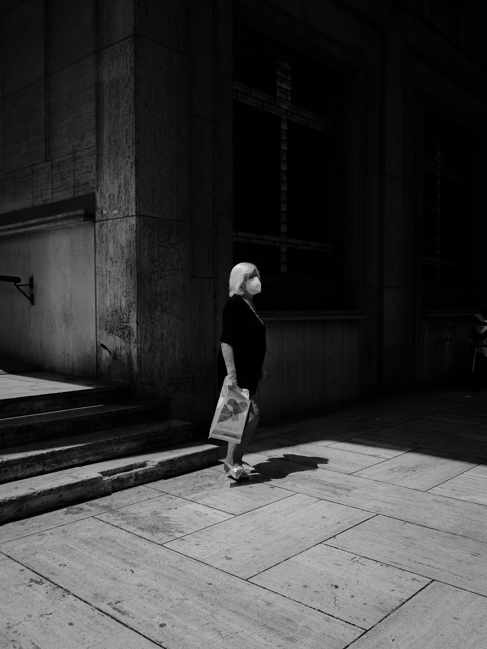 grayscale photo of man in black shirt and pants walking on sidewalk