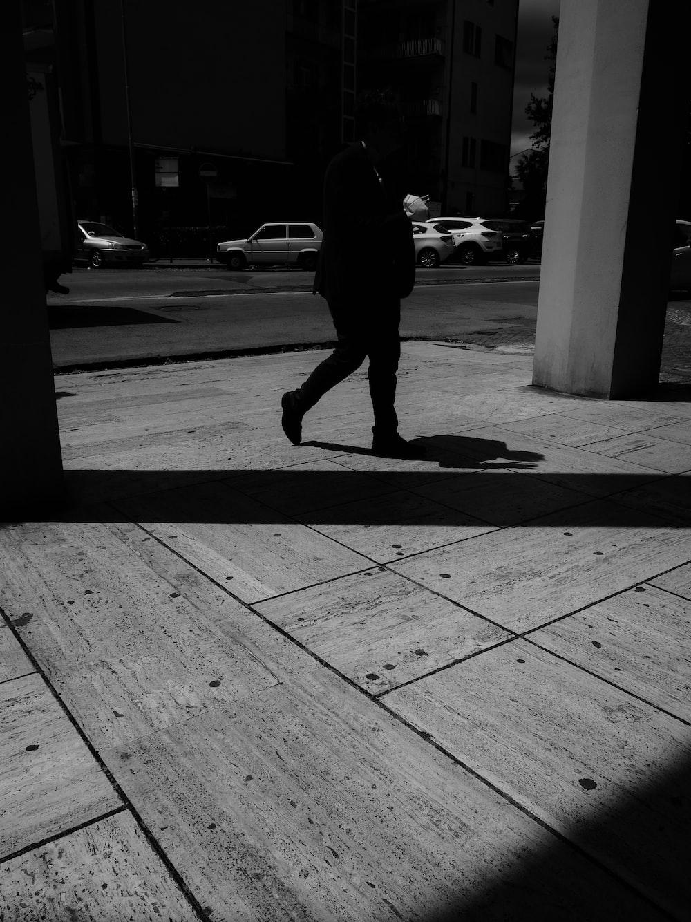 man in black jacket walking on sidewalk