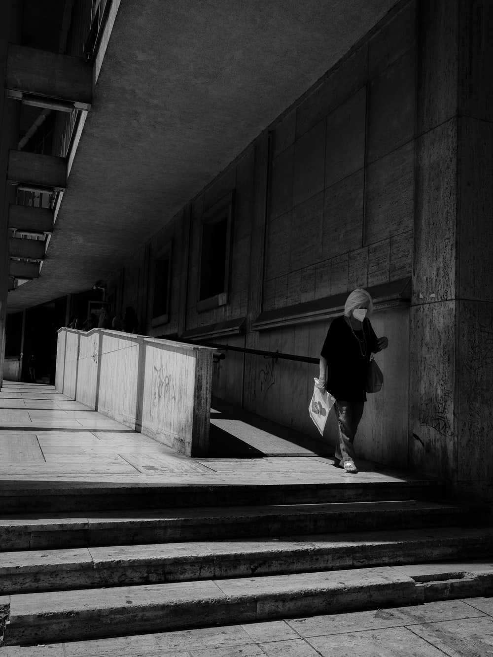 grayscale photo of woman in black long sleeve shirt and pants walking on hallway