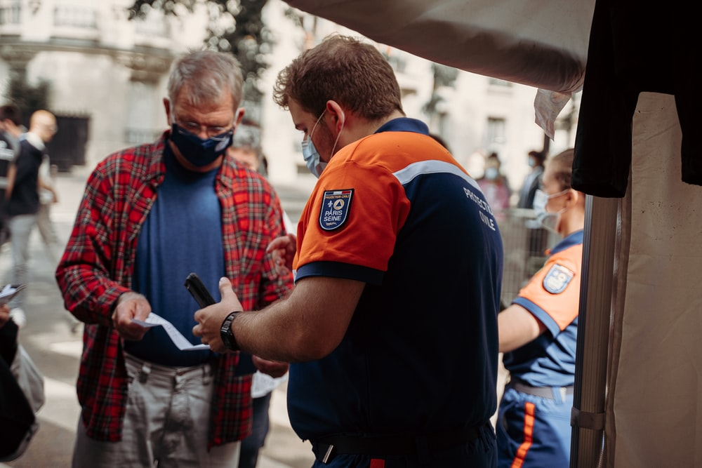 man in blue and orange polo shirt holding black smartphone