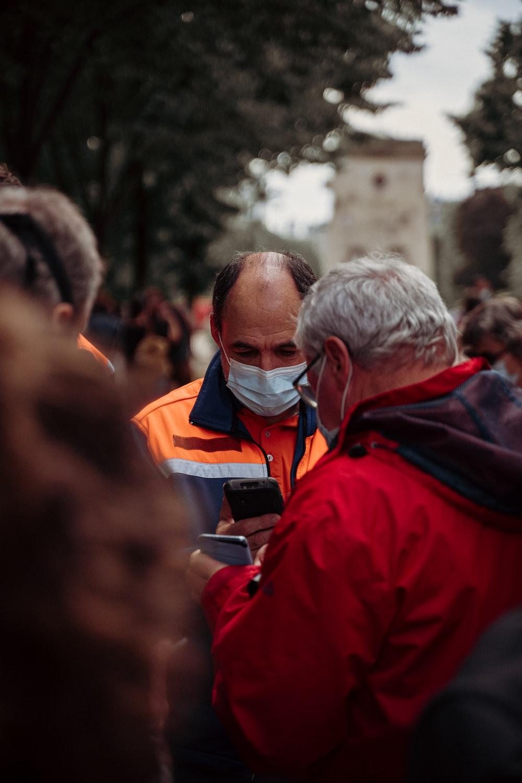 man in red jacket wearing white mask