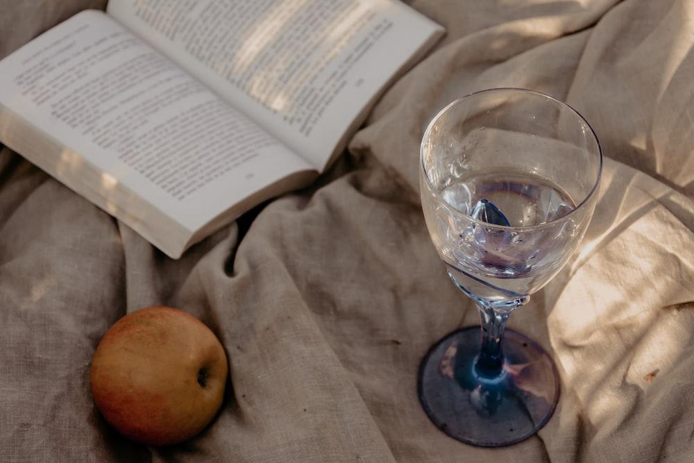 clear wine glass beside apple fruit