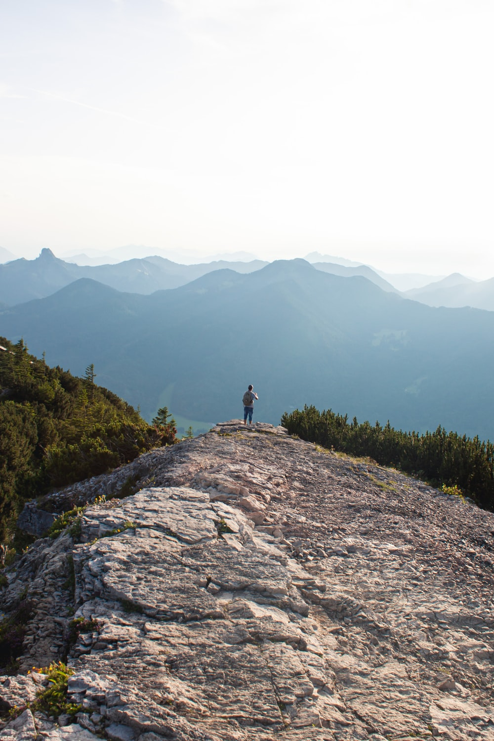 person standing on rock mountain during daytime