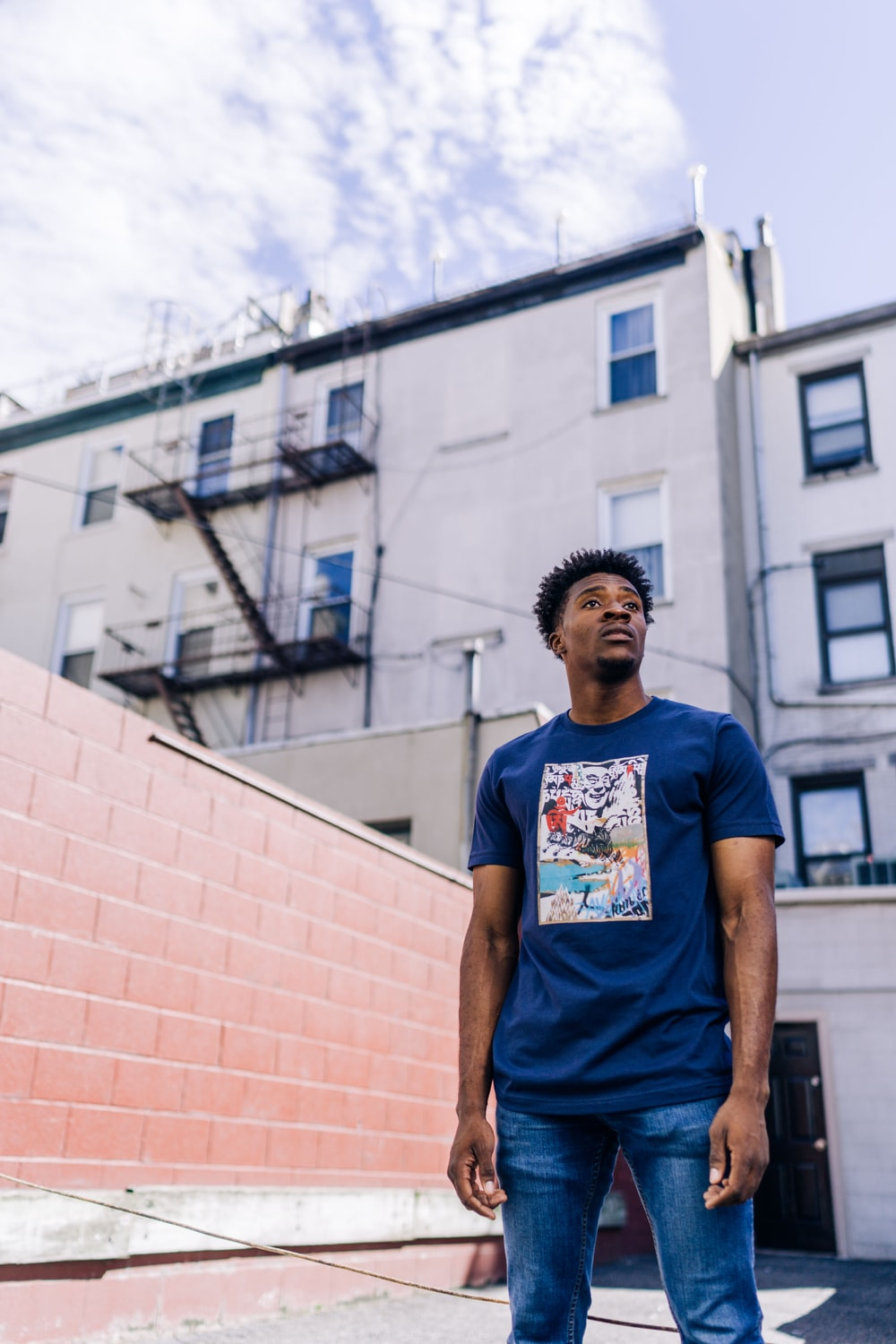 man in blue crew neck t-shirt standing near brown concrete building during daytime