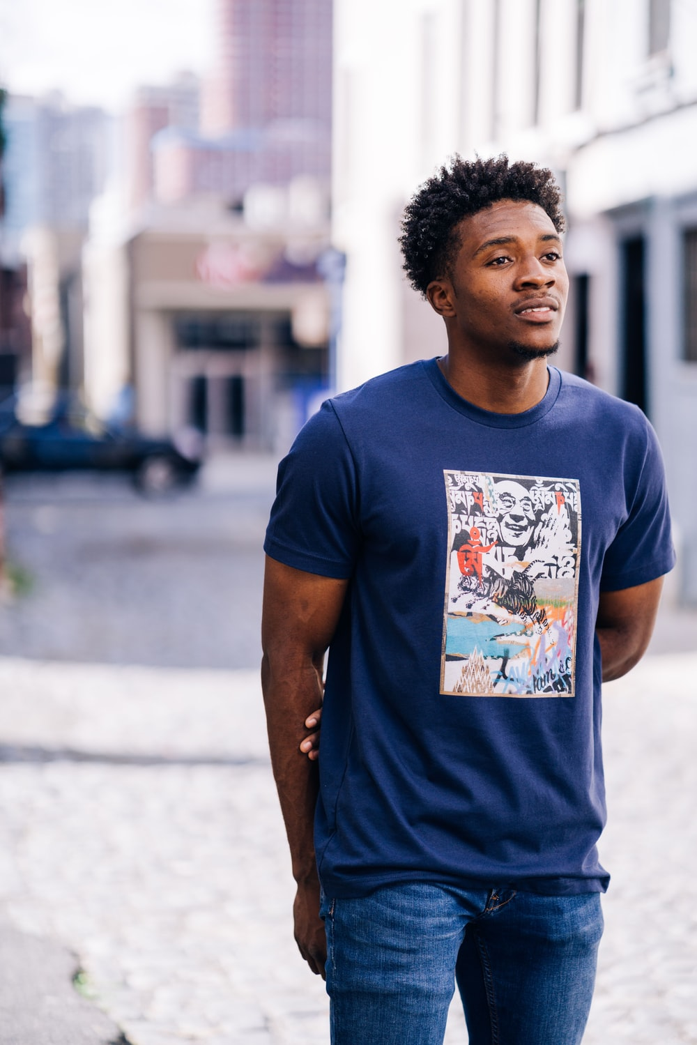 man in blue crew neck t-shirt standing on road during daytime