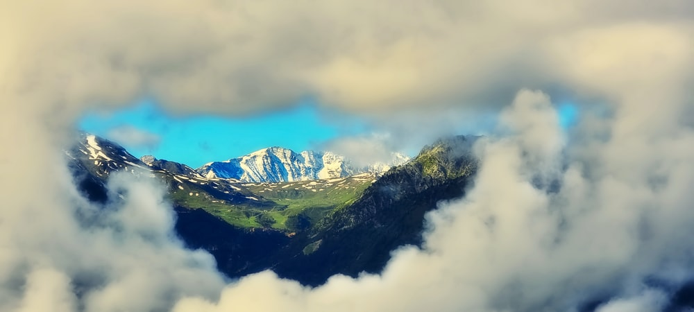 green and white mountains under white clouds during daytime