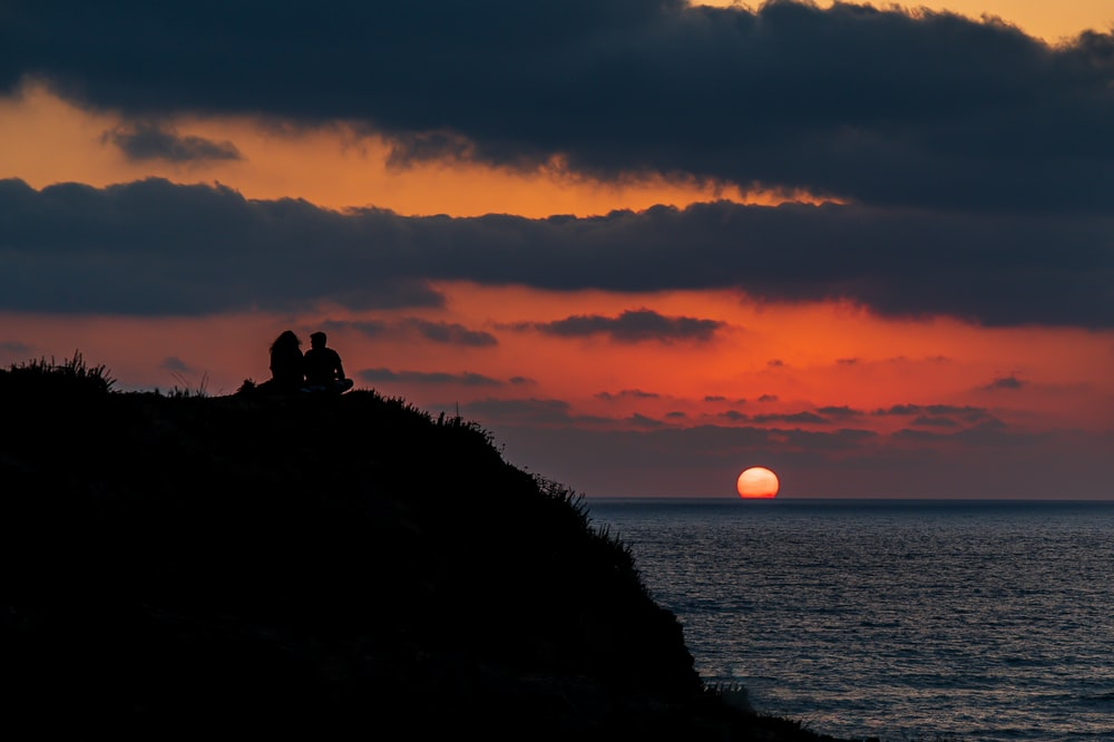 silhouette of 2 people sitting on rock formation during sunset
